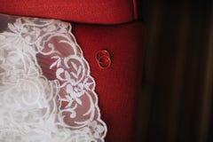 alianças de casamento em vestidos de casamento do sofá do vermelho fotos de stock royalty free