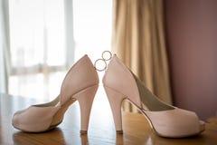 Alianças de casamento entre sapatas do rosa do ` s da noiva ceremony imagens de stock
