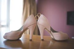Alianças de casamento entre sapatas do rosa do ` s da noiva ceremony imagem de stock royalty free