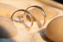 Alianças de casamento na areia com pedras Foto de Stock Royalty Free
