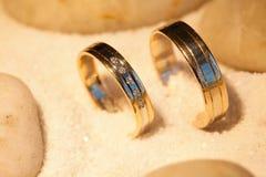 Alianças de casamento na areia com pedras Imagens de Stock Royalty Free