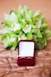 Alianças de casamento na caixa vermelha no ramalhete verde Foto de Stock