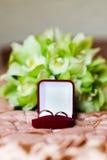 Alianças de casamento na caixa vermelha no ramalhete verde Imagem de Stock Royalty Free