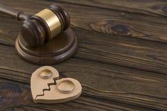 Alianças de casamento na figura de um coração quebrado de uma árvore, martelo de um juiz em um fundo de madeira Fotografia de Stock