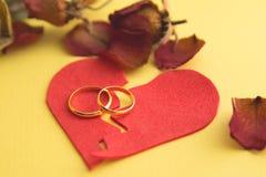 Alianças de casamento na figura de um coração quebrado de uma árvore, martelo de um juiz em um fundo de madeira divórcio fotos de stock royalty free