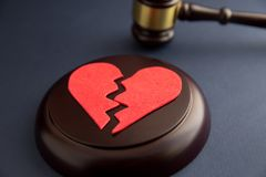 Alianças de casamento na figura de um coração quebrado de uma árvore, martelo de um juiz em um fundo de madeira divórcio imagens de stock