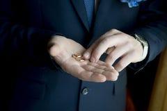 Alianças de casamento na palma do noivo imagem de stock