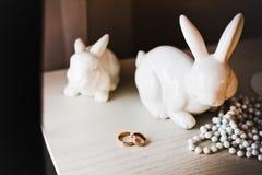 Alianças de casamento na tabela com lebres Fotos de Stock Royalty Free
