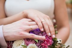 Alianças de casamento nas mãos dos recém-casados, ramalhete do casamento, Br fotografia de stock royalty free