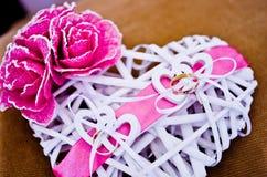 Alianças de casamento no coração branco fotografia de stock royalty free
