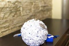 Alianças de casamento no coxim, descanso para anéis sob a forma de um ramalhete das rosas, parafernália do casamento, um símbolo  Imagens de Stock Royalty Free