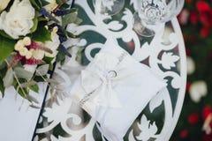 Alianças de casamento no descanso branco imagens de stock