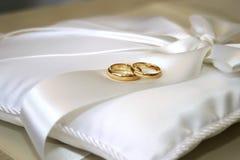 Alianças de casamento no descanso branco do cetim Imagem de Stock