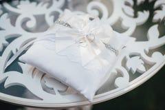 Alianças de casamento no descanso branco na tabela da cerimônia foto de stock