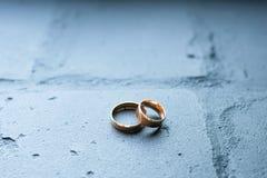 Alianças de casamento no fundo azul do tijolo o ouro soa o amor e o casamento do ol do conceito imagem de stock