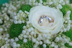 Alianças de casamento no fundo das flores fotografia de stock