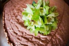 Alianças de casamento no ramalhete do casamento e em uma cama verde Imagens de Stock Royalty Free