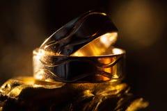Alianças de casamento nos raios da luz amarela Fotografia de Stock