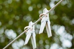 Alianças de casamento que penduram em uma corda fotografia de stock
