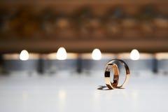 Alianças de casamento em um fundo de velas ardentes Fotografia de Stock Royalty Free