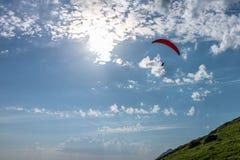 Aliante rosso in cielo nuvoloso blu sopra la montagna verde fotografie stock libere da diritti