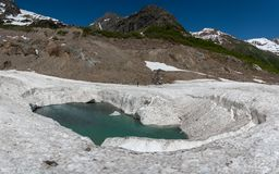 Alibek highland river in the middle of avalanches in summer. In the Karachay-Cherkess Republic, Russia stock photography