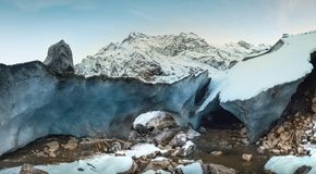 Alibek snow-covered mountain and the base of the glacier and the entrance to the ice cave stock photography