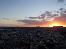 Alicante solnedgång med berg bak stad Arkivbilder