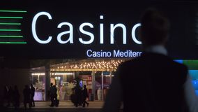 People walking in the street with gambling house at night. Alicante, Spain stock footage