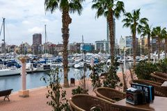 ALICANTE, SPAIN - April 26, 2018: view from a cafe with rattan furniture on a port with yachts and a waterfront royalty free stock images