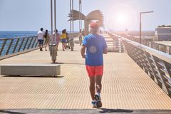 ALICANTE, SPAIN, CIRCA JUNE 2018, Active senior man jogging on the pier royalty free stock images