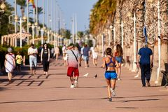 ALICANTE, SPAIN, CIRCA JUNE 2018 People walking and running on the promenade royalty free stock photos