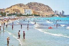 Tourists sunbathing on a Postiguet Beach of Alicante city. Spain Royalty Free Stock Images