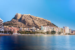Alicante in Spain. Alicante sandy beach with Santa Barbara castle. Blurred water royalty free stock images