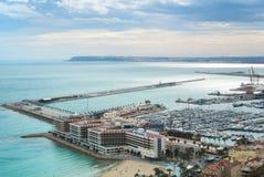 ALICANTE SPANIEN - FEBRUARI 12, 2016: En sikt från Santa Barbara Castle till en port av staden med ett överflöd av yachter Arkivfoton