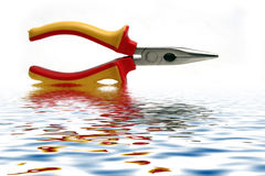 Alicate. Red and yellow tool in water with reflex Royalty Free Stock Images