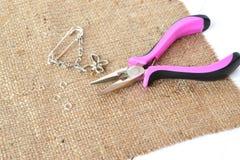 Alicates, corrente, anéis do metal e pendentes em um fundo de madeira branco Como fazer você mesmo broche do metal fotografia de stock royalty free