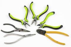 Alicates e cortadores do cabo em uma tabela branca Acessórios para DIY e Imagem de Stock