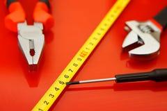Alicates, fita métrica, chave da cabo-cabeça e mentira da chave de fenda-torneira na superfície lustrada vermelha na loja de repa foto de stock