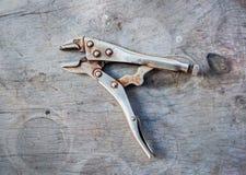 Alicates velhos do aperto do fechamento na madeira fotografia de stock