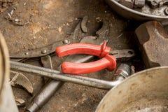 Alicates viejos grasientos con la llave inglesa del cortador de alambre y de la llave ajustable en la tierra sucia fotografía de archivo