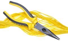 Alicates y cables amarillos Imagenes de archivo