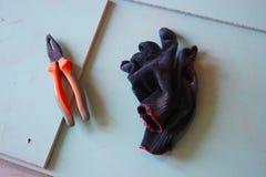 Alicates y guantes en el fondo de la mampostería seca reparación del apartamento y de la casa, construcción momentos de trabajo e foto de archivo