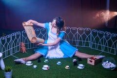 Alice betrachtet eine Rolle mit einer Karte Lizenzfreie Stockfotos