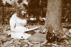 Alice che legge un libro Fotografie Stock