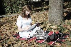 Alice che legge un libro immagine stock