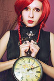 Alice with clock. Redhead redeyed pretty girl posing with clock over violent background Stock Photography