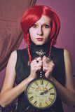 Alice with clock. Redhead redeyed pretty girl posing with clock over violent background Stock Photos