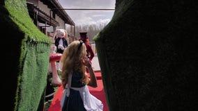 Alice en de Hoedenmaker van Alice in Sprookjesland lopen langs de fabelachtige gang De camera volgt prachtig de karakters stock video