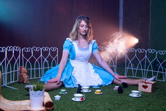 Alice fell and landed in Wonderland. Alice fell and landed on a glade in Wonderland Stock Photo